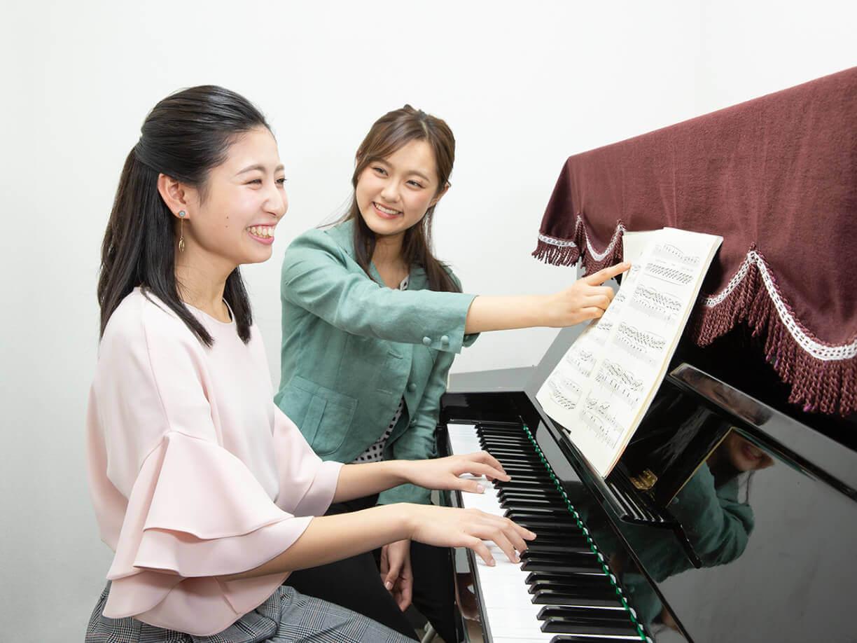 ピアノを教えてもらう女性